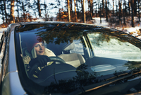 Beautiful woman in warm clothing driving car 11016033194| 写真素材・ストックフォト・画像・イラスト素材|アマナイメージズ
