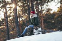 Woman looking away while sitting on log during winter 11016033196| 写真素材・ストックフォト・画像・イラスト素材|アマナイメージズ