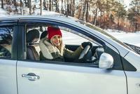 Portrait of smiling woman in warm clothing driving car 11016033198| 写真素材・ストックフォト・画像・イラスト素材|アマナイメージズ