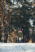 Full length of woman walking in snow covered forest 11016033199| 写真素材・ストックフォト・画像・イラスト素材|アマナイメージズ
