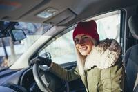 Portrait of happy woman in warm clothing driving car 11016033202| 写真素材・ストックフォト・画像・イラスト素材|アマナイメージズ