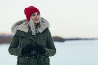 Thoughtful woman with camera enjoying winter season 11016033204| 写真素材・ストックフォト・画像・イラスト素材|アマナイメージズ