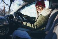 Portrait of happy young woman in warm clothing driving car 11016033205| 写真素材・ストックフォト・画像・イラスト素材|アマナイメージズ