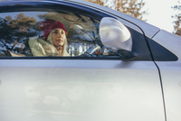 Low angle view of woman driving car during winter 11016033210| 写真素材・ストックフォト・画像・イラスト素材|アマナイメージズ