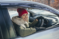 Portrait of happy beautiful woman driving car during winter 11016033215| 写真素材・ストックフォト・画像・イラスト素材|アマナイメージズ