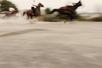 Blurred motion of people riding horses on road, Sedilo, Sardinia, Italy 11016033238| 写真素材・ストックフォト・画像・イラスト素材|アマナイメージズ