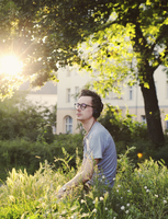 Man enjoying music through headset while sitting in park 11016033273| 写真素材・ストックフォト・画像・イラスト素材|アマナイメージズ