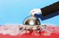 Cropped image of waiter lifting domed tray against blue background 11016033280| 写真素材・ストックフォト・画像・イラスト素材|アマナイメージズ