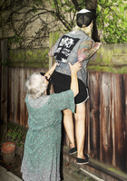 Mother helping daughter in climbing wooden fence at back yard 11016033292| 写真素材・ストックフォト・画像・イラスト素材|アマナイメージズ