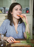 Portrait of happy woman eating carrot while sitting at table 11016033299| 写真素材・ストックフォト・画像・イラスト素材|アマナイメージズ