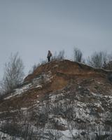 Low angle view of hiker standing on mountain peak during winter 11016033313| 写真素材・ストックフォト・画像・イラスト素材|アマナイメージズ