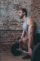 Determined young man lifting barbell at gym 11016033319| 写真素材・ストックフォト・画像・イラスト素材|アマナイメージズ