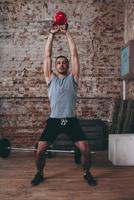 Full length of man lifting kettlebell at gym 11016033322| 写真素材・ストックフォト・画像・イラスト素材|アマナイメージズ
