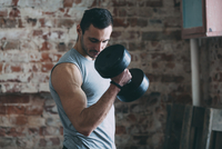 Determined young man lifting dumbbell at gym 11016033328| 写真素材・ストックフォト・画像・イラスト素材|アマナイメージズ