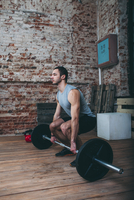 Determined young man lifting barbell at health club 11016033331| 写真素材・ストックフォト・画像・イラスト素材|アマナイメージズ