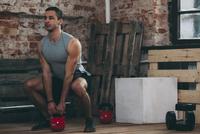 Determined man lifting kettlebell at gym 11016033333| 写真素材・ストックフォト・画像・イラスト素材|アマナイメージズ