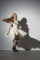 Full length portrait of woman spinning against white background 11016033341| 写真素材・ストックフォト・画像・イラスト素材|アマナイメージズ