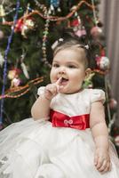 Cute baby girl sitting with Christmas tree in background 11016033353| 写真素材・ストックフォト・画像・イラスト素材|アマナイメージズ