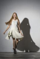 Portrait of woman spinning against white background 11016033366| 写真素材・ストックフォト・画像・イラスト素材|アマナイメージズ