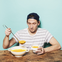 Mid adult man serving pumpkin soup in bowl at table against blue background 11016033423| 写真素材・ストックフォト・画像・イラスト素材|アマナイメージズ