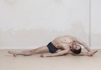 Flexible man performing revolved head-to-knee yoga pose 11016033441| 写真素材・ストックフォト・画像・イラスト素材|アマナイメージズ
