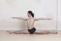 Confident man with arms outstretched doing splits while performing yoga 11016033443| 写真素材・ストックフォト・画像・イラスト素材|アマナイメージズ