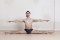 Man with arms outstretched doing splits while performing yoga against white background 11016033445| 写真素材・ストックフォト・画像・イラスト素材|アマナイメージズ
