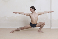 Determined man practicing yoga in warrior position against white background 11016033446| 写真素材・ストックフォト・画像・イラスト素材|アマナイメージズ
