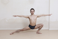 Portrait of determined man practicing yoga in warrior position against white background 11016033450| 写真素材・ストックフォト・画像・イラスト素材|アマナイメージズ