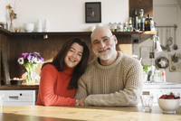Portrait of mature couple sitting by table at home 11016033490| 写真素材・ストックフォト・画像・イラスト素材|アマナイメージズ