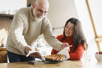 Mature man serving pie to wife on table at home 11016033494| 写真素材・ストックフォト・画像・イラスト素材|アマナイメージズ