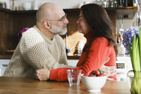 Mature couple embracing by table in kitchen at home 11016033495| 写真素材・ストックフォト・画像・イラスト素材|アマナイメージズ
