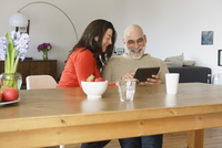 Mature couple smiling while looking at digital tablet at wooden table 11016033497| 写真素材・ストックフォト・画像・イラスト素材|アマナイメージズ