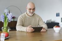 Smiling mature man using digital tablet on table at home 11016033501| 写真素材・ストックフォト・画像・イラスト素材|アマナイメージズ