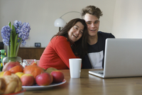 Happy mother and son sitting with laptop on table at home 11016033502| 写真素材・ストックフォト・画像・イラスト素材|アマナイメージズ