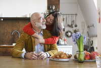 Happy couple embracing and smiling by table at home 11016033509| 写真素材・ストックフォト・画像・イラスト素材|アマナイメージズ