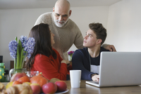 Family talking by table with laptop at home 11016033511| 写真素材・ストックフォト・画像・イラスト素材|アマナイメージズ
