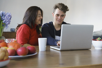 Smiling mother and son using laptop on table at home 11016033517| 写真素材・ストックフォト・画像・イラスト素材|アマナイメージズ