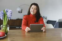 Mature woman looking away while holding digital tablet on table at home 11016033519| 写真素材・ストックフォト・画像・イラスト素材|アマナイメージズ