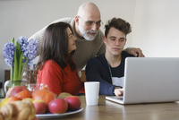 Family discussing while looking at laptop on table at home 11016033520| 写真素材・ストックフォト・画像・イラスト素材|アマナイメージズ