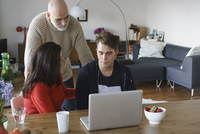 Parents talking with son by table with laptop at home 11016033523| 写真素材・ストックフォト・画像・イラスト素材|アマナイメージズ