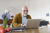 Smiling mature man using laptop on table at home 11016033525| 写真素材・ストックフォト・画像・イラスト素材|アマナイメージズ