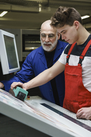 Workers checking quality of print with scanner at printing press