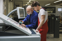 Mature worker showing colleague quality of printout with scanner at printing press