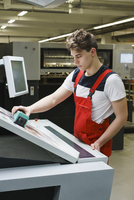 Young worker checking quality of printout with scanner at printing press