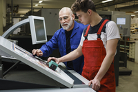 Mature man and coworker doing quality check of printout with machinery at printing press 11016033542| 写真素材・ストックフォト・画像・イラスト素材|アマナイメージズ