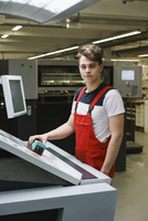 Portrait of young worker holding scanner over printout with machinery at printing press