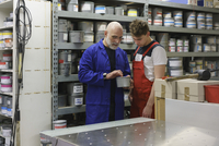 Mature man talking with coworker in printing workshop