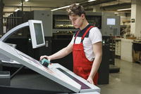 Young worker doing quality check of printout with machinery at printing press