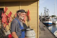 Senior man standing at harbor by boats moored at lake 11016033569| 写真素材・ストックフォト・画像・イラスト素材|アマナイメージズ